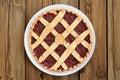 Lattice round cake with strawberry jam on wooden background Royalty Free Stock Photo