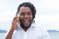 Laughing african american guy with dreadlocks and white shirt at phone Royalty Free Stock Photo