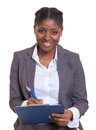 Laughing African business woman with clipboard
