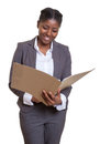 Laughing african business woman reading file Royalty Free Stock Photo