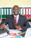 Laughing african businessman at his office happy with tie and dark suit looking camera Royalty Free Stock Photography