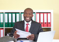 Laughing african businessman reading a letter attractive with tie and dark suit at his office at camera with in his hand Stock Photo