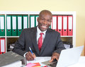 Laughing african businessman writing a message with tie and dark suit at his office Stock Images