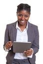 Laughing african businesswoman working with tablet computer Royalty Free Stock Photo
