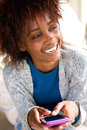 Laughing african woman holding mobile phone Royalty Free Stock Photo