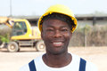 Laughing african worker at construction site with looking camera yellow excavator in the background Stock Images