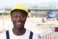 Laughing african worker at construction zone looking at camera with excavator in the background Royalty Free Stock Images