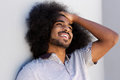 Laughing afro man with hand in hair looking away Royalty Free Stock Photo