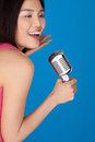 Laughing Asian woman with a microphone Royalty Free Stock Image