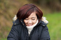 Laughing attractive young asian woman walking outdoors on a cold day snuggling down into her warm polo neck sweater and jacket Royalty Free Stock Image