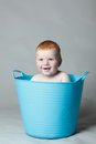Laughing baby in a blue bucket this image has attached release Royalty Free Stock Photography