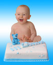 Laughing baby with cake surprise on blue background Stock Photo
