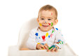 Laughing baby with colorful paints on face and hands sitting in a high chair against white background Stock Photo