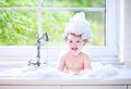 Laughing baby girl playing in big kitchen sink with foam funny little wet curly hair taking a bath a lots of water drops and Stock Image