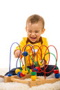 Laughing baby having fun with toy boy wooden on fur carpet Royalty Free Stock Images