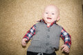Laughing baby wearing gray vest and plaid shirt a happy with a big smile blue eyes a red white blue Royalty Free Stock Photography