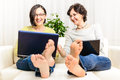 Laughing barefoot funny happy women chat browsing home laptop Royalty Free Stock Photo