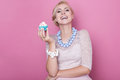 Laughing beautiful women hold little colorful cake. Soft colors Royalty Free Stock Photo