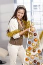 Laughing beauty decorating christmas tree modern and design with bulb holding garland smiling looking away Royalty Free Stock Photo