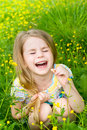 Laughing blond little girl with closed eyes sitting in the grass vertical portrait of a Stock Photo