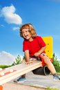 Laughing boy on seesaw happy little three years old child sitting and the Royalty Free Stock Image