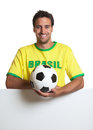 Laughing brazilian soccer fan with ball behind signboard Royalty Free Stock Photo
