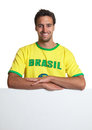 Laughing brazilian soccer fan behind signboard Royalty Free Stock Photo