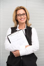 Laughing business woman in white shirt attractive mature businesswoman with clipboard before shutters smiling Royalty Free Stock Photos