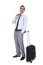Laughing businessman standing next to his suitcase on white background Royalty Free Stock Photo