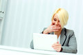 Laughing businesswoman sitting at the table and holding tablet compute computer in office Royalty Free Stock Photos