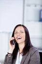 Laughing businesswoman talking through her cellular phone inside the office Stock Photography