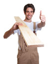 Laughing carpenter with wooden beam showing thumb on an isolated white background for cut out Royalty Free Stock Image