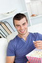 Laughing caucasian man eating popcorn on the sofa Royalty Free Stock Image