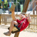 Laughing child in red dres on chain swing playground Royalty Free Stock Image