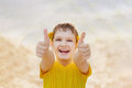 Laughing child with yellow dandelion in his ears, showing thumbs Royalty Free Stock Photo