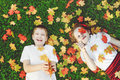 Laughing children lying in grass throwing the autumn leaves in t Royalty Free Stock Photo