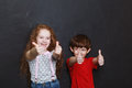 Laughing children showing thumbs up.