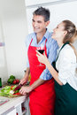 Laughing couple cooking in kitchen a happy caucasian the food and drinking wine Stock Photography