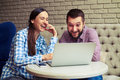 Laughing couple looking at laptop at home portrait of Royalty Free Stock Image