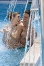 Laughing couple standing under swimming pool shower Stock Images