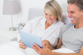 Laughing couple using tablet pc in bed together at home bedroom Royalty Free Stock Photo