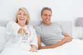 Laughing couple watching tv in bed at home bedroom Royalty Free Stock Photos