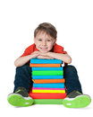 Laughing cute boy with books a is sitting on the floor near the pile of on the white background Stock Images