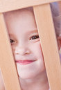 Laughing cute little girl in the crib adorable looking out of Stock Images