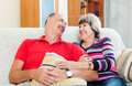 Laughing elderly couple relaxing on couch Royalty Free Stock Photos