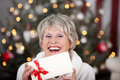 Laughing elderly lady with an xmas gift voucher holding the blank white envelope as she sits in front of the christmas tree Royalty Free Stock Photography