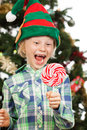 Laughing elf looking at lollipo a happy boy dressed as santas helper or an is holding and a big red lollipop isolated on white Stock Images
