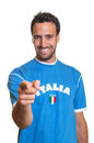 Laughing fan from italy pointing at camera sports with a blue jersey on a white background Royalty Free Stock Photography