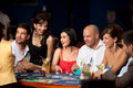 Laughing friends playing cards in a casino Stock Photos