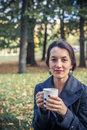 Laughing girl in an autumn part with a white cup of hot drink Stock Photos